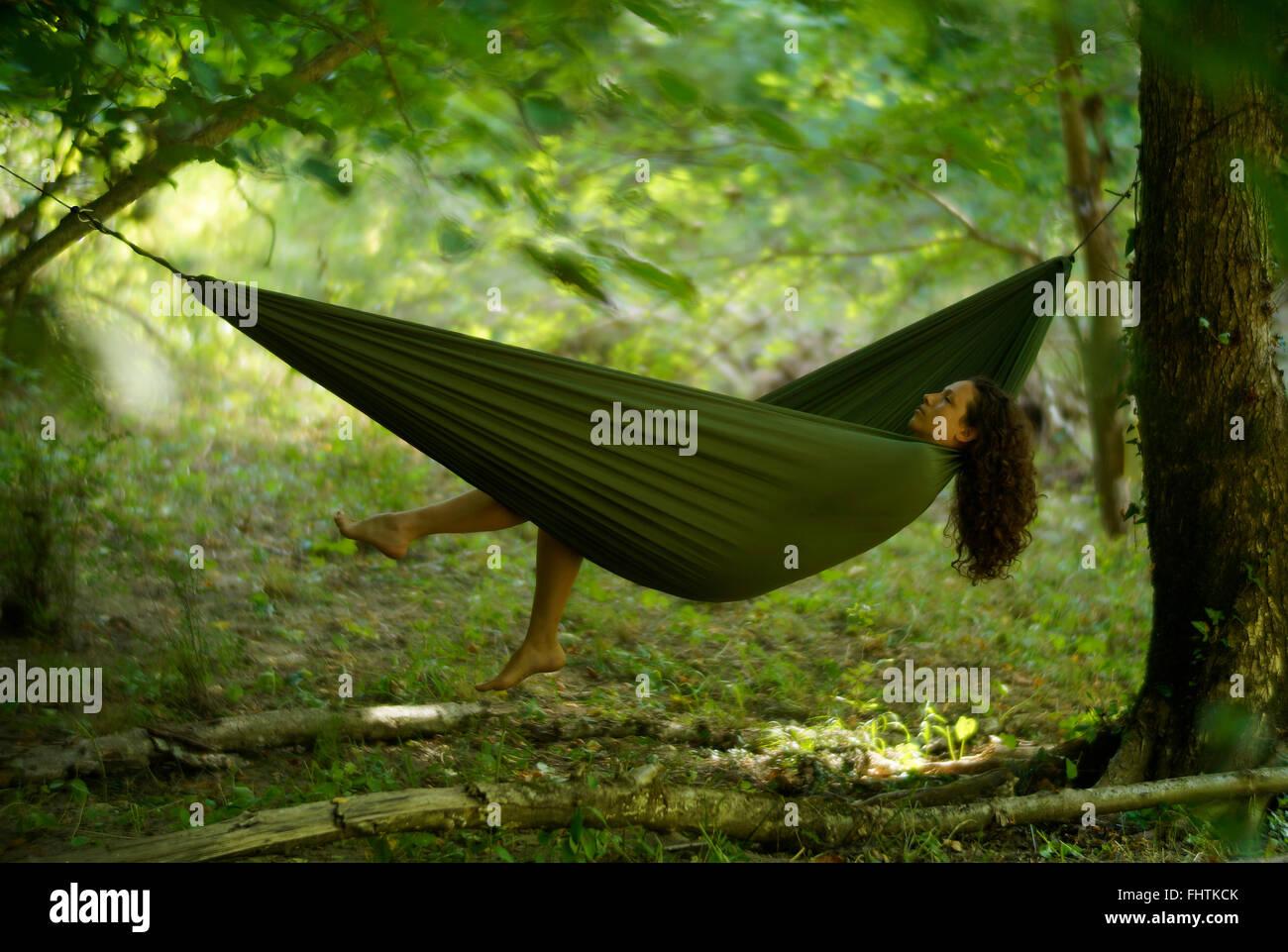 Schöne junge Frau in einer Hängematte entspannen tief im Wald. Stockbild