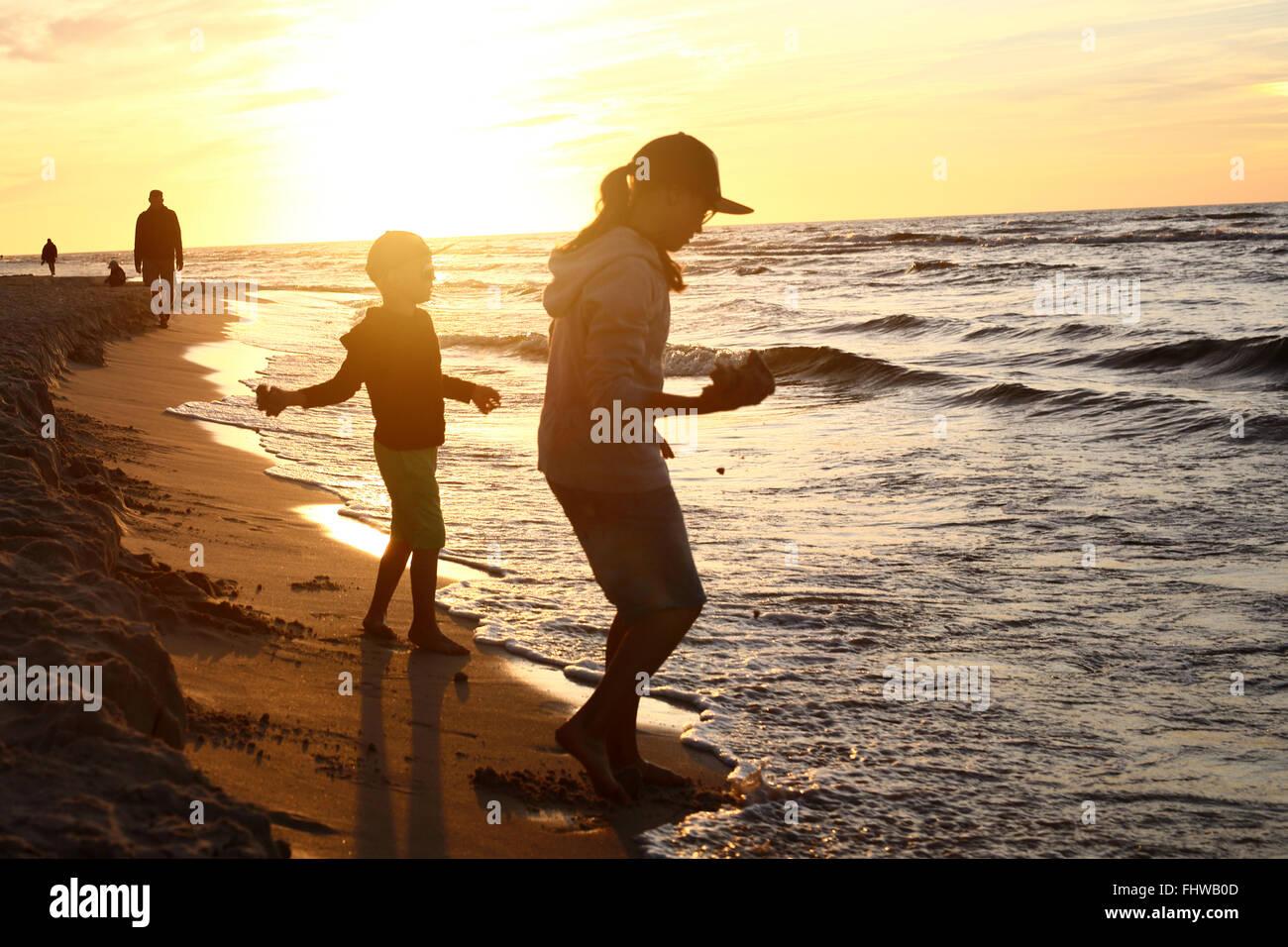 Walking am Strand, Sonnenuntergang. Kinder Jungen und Mädchen spielen am Ufer Meeres auf einem sandigen Strand Stockbild