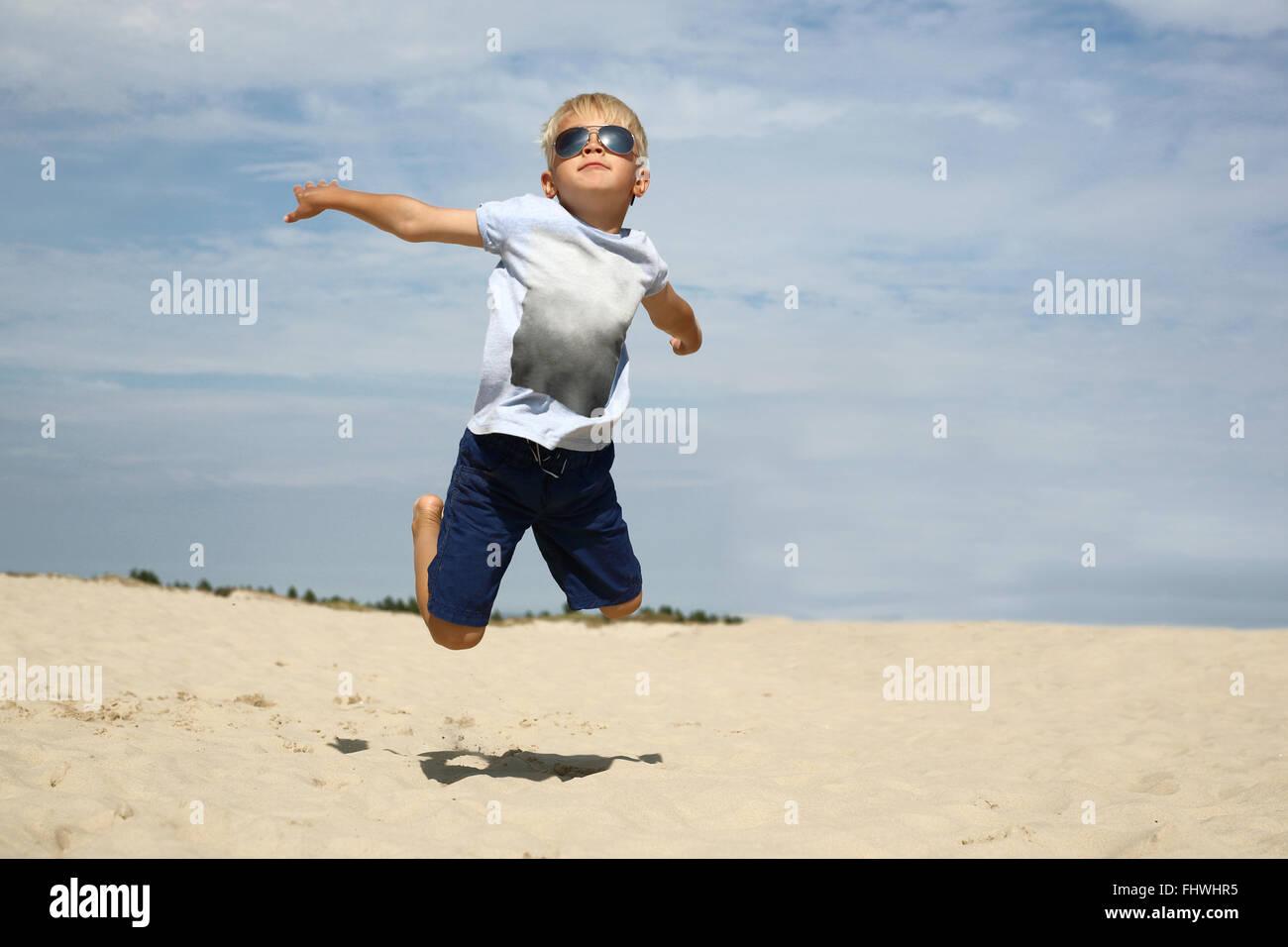 Ich kann fliegen! Der junge springt auf den Sandstrand. Urlaub! Stockbild