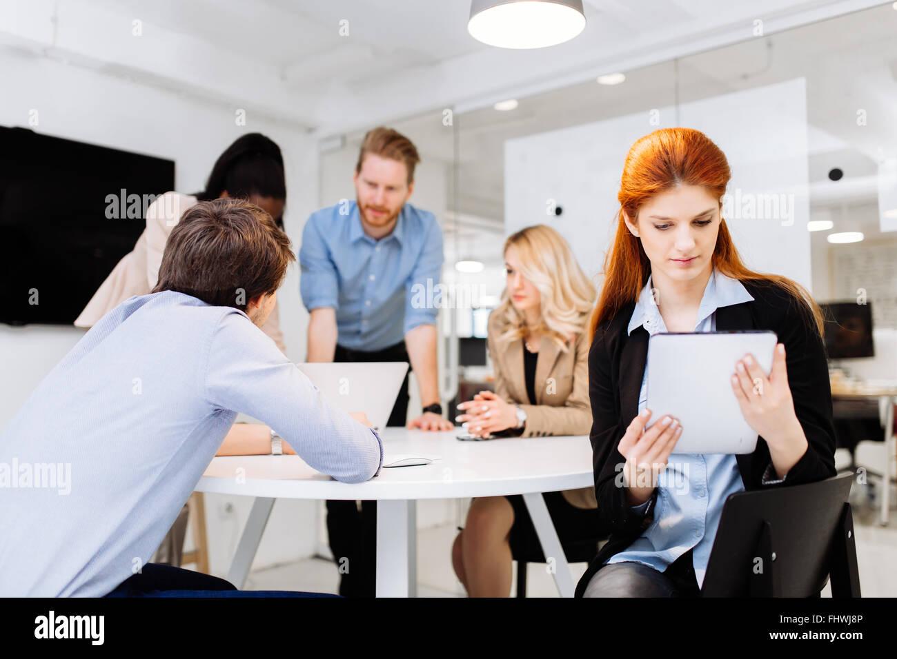 Geschäftskollegen mit Technologie griffbereit am Schreibtisch sitzen Stockbild