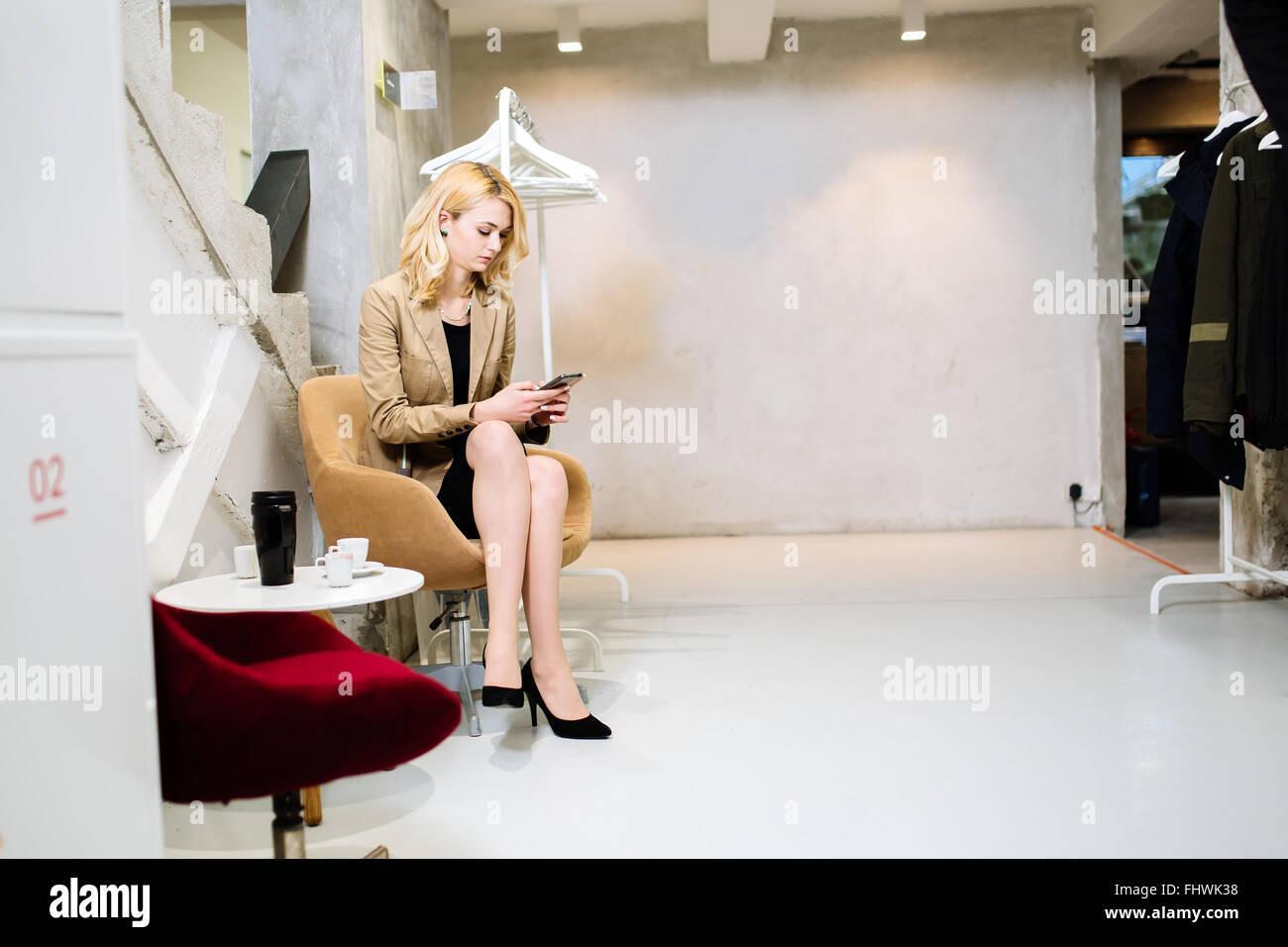 Geschäftsfrau, die im Korridor zu brechen und mit Telefon Stockbild