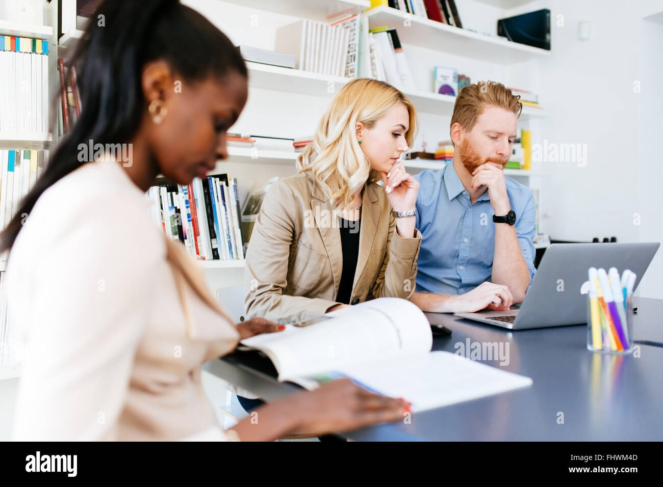 Multiethnische Menschen arbeiten in modernen, gut ausgestatteten Büro Stockbild