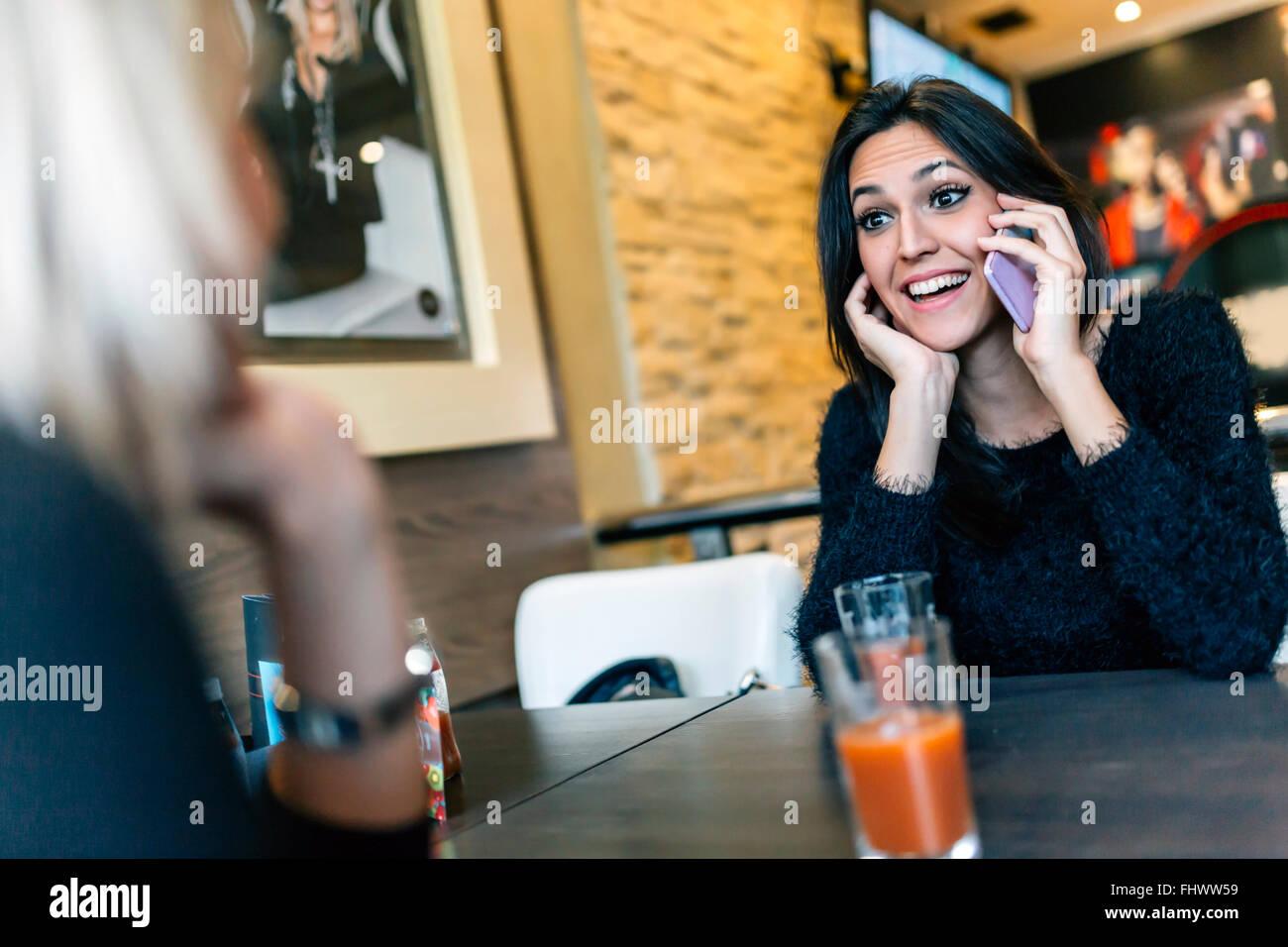 Schöne Brünette im Café begleitet von Freund telefonieren Stockbild
