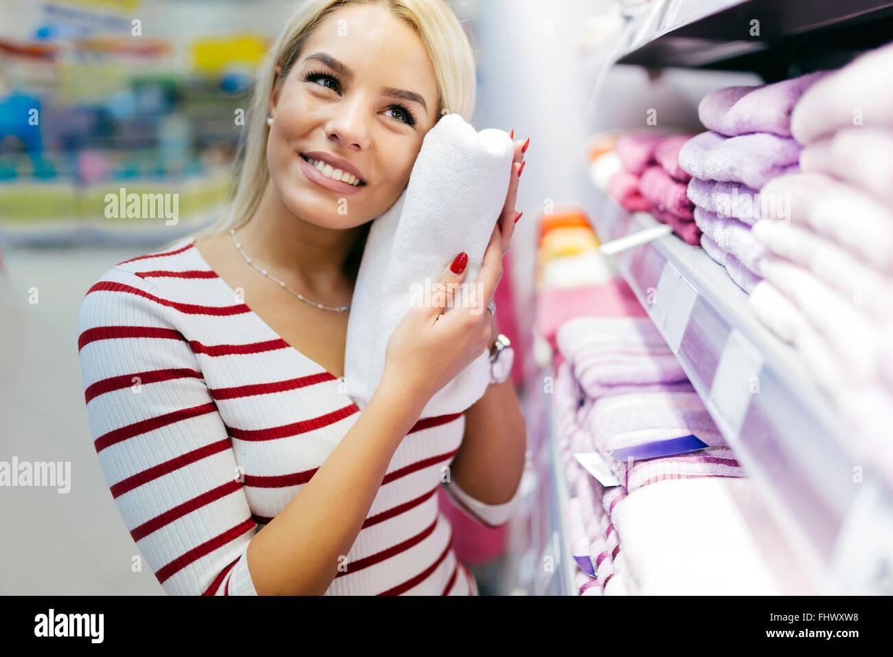 Schöne Frau, Inspektion und Handtücher im Supermarkt zu kaufen Stockbild