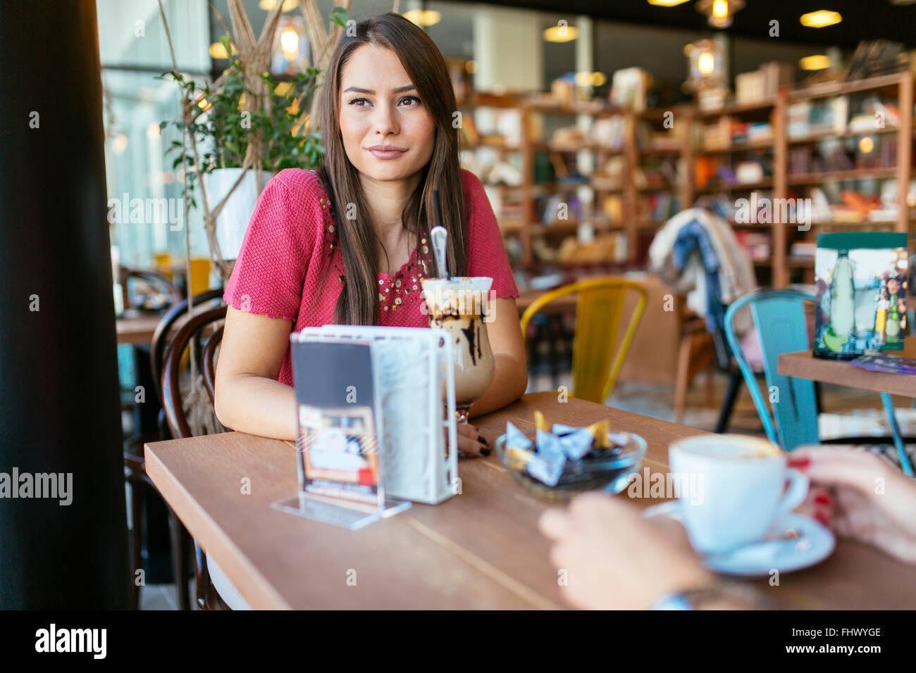 Schöne Frau im Gespräch mit Freund im Restaurant beim Kaffeetrinken Stockbild