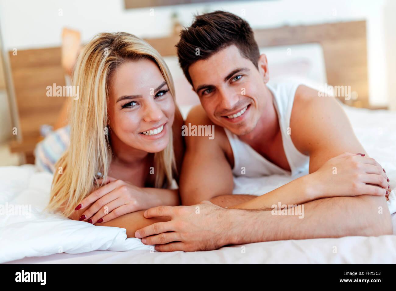 Glücklicher Ehemann liebende Ehefrau beim liegen im Bett Stockbild