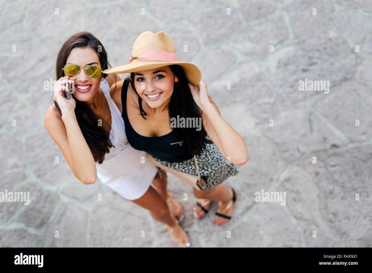 Schöne Freunde outdoor-Spaß und telefonieren Stockbild