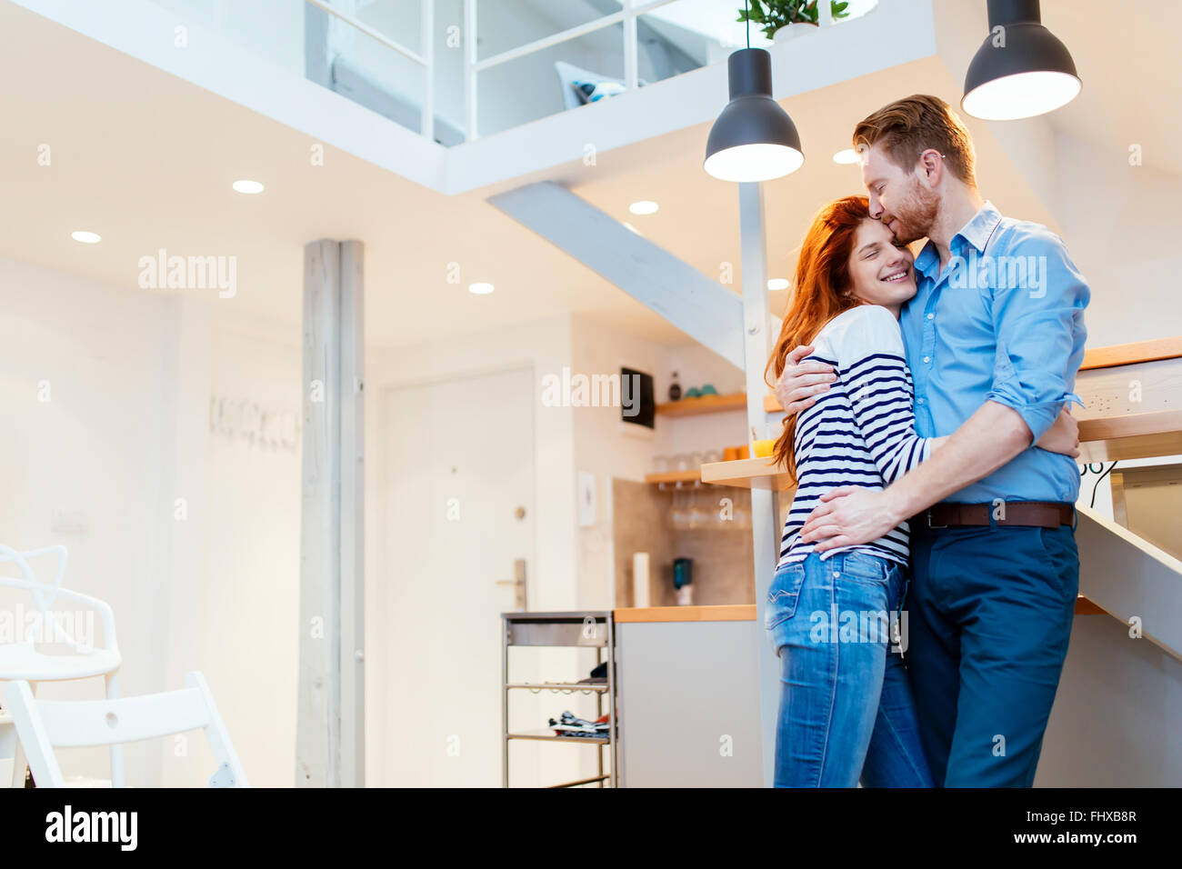 Paar genießt ihr neue luxuriöseste Zuhause und umarmt im Wohnzimmer Stockbild