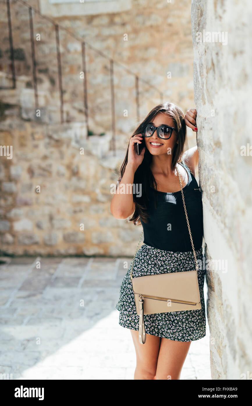 Attraktive Frau posiert während des Gesprächs am Telefon im Freien im Sommer Stockbild