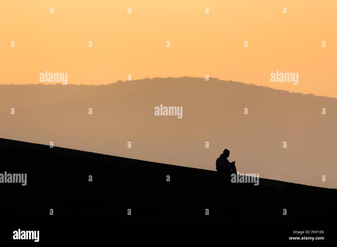 Mann auf einem Dach, von ihm selbst sein Smartphone überprüfen und mit einer Zigarette Stockbild