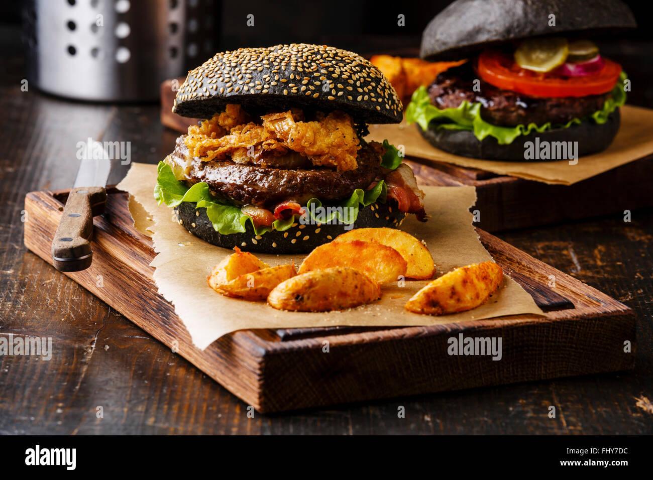 Schwarzen Burger mit Sesam Samen Brötchen Fleisch Speck Zwiebeln Pommes frites, Ringe und Kartoffelspalten Stockbild