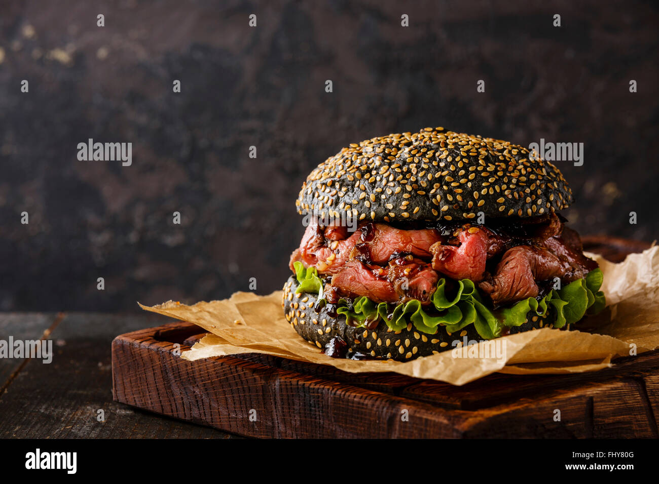 Roast Beef Burger Imbiss Snack auf Sesam Brötchen mit in Scheiben geschnittenen Pastrami auf schwarzem Hintergrund Stockbild