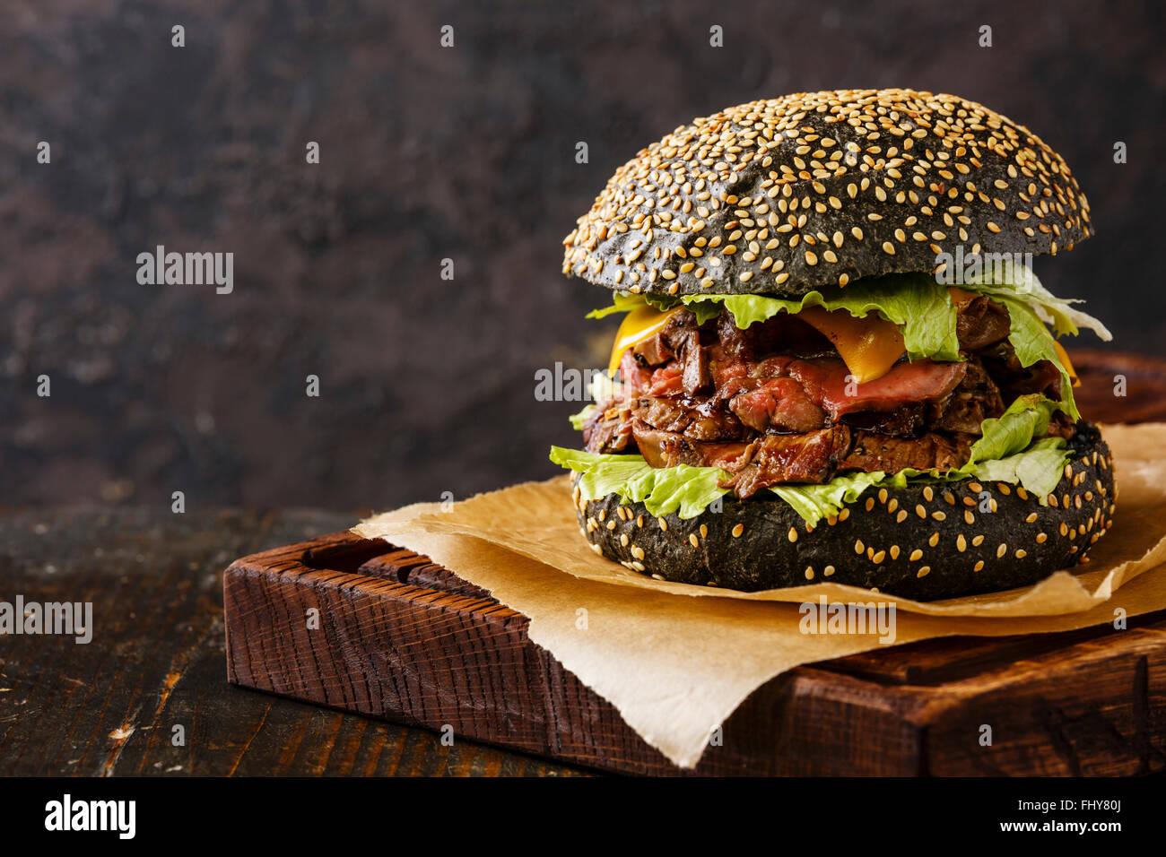 Roast Beef Burger auf Sesam Brötchen mit in Scheiben geschnittenen Pastrami auf schwarzem Hintergrund Stockbild