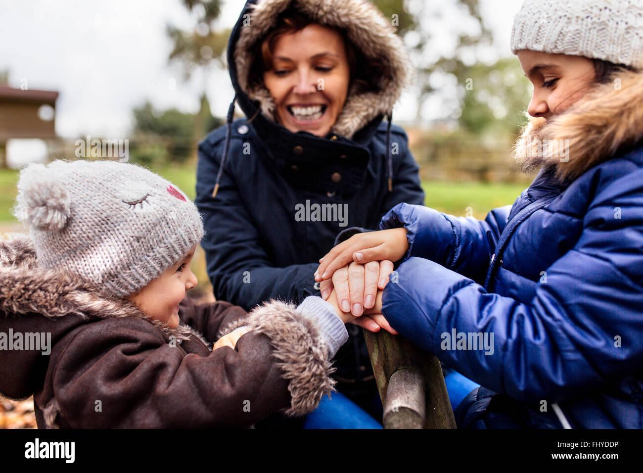Zwei kleine Schwestern mit ihrer Mutter auf einem Spielplatz im Herbst Stockbild