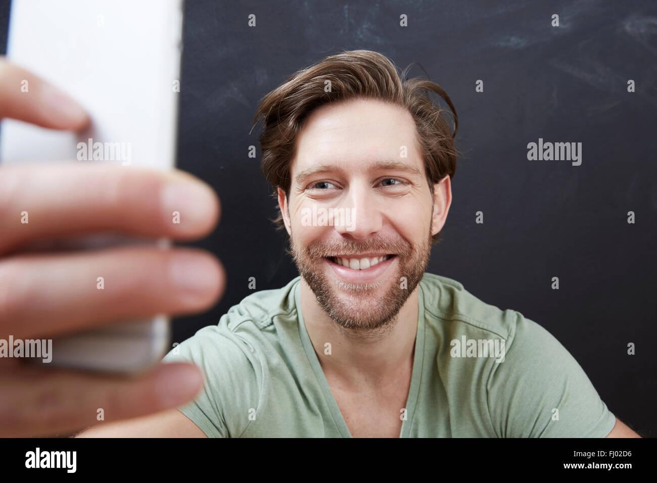 Porträt von lächelnden jungen Mann unter ein Selbstporträt mit smartphone Stockbild