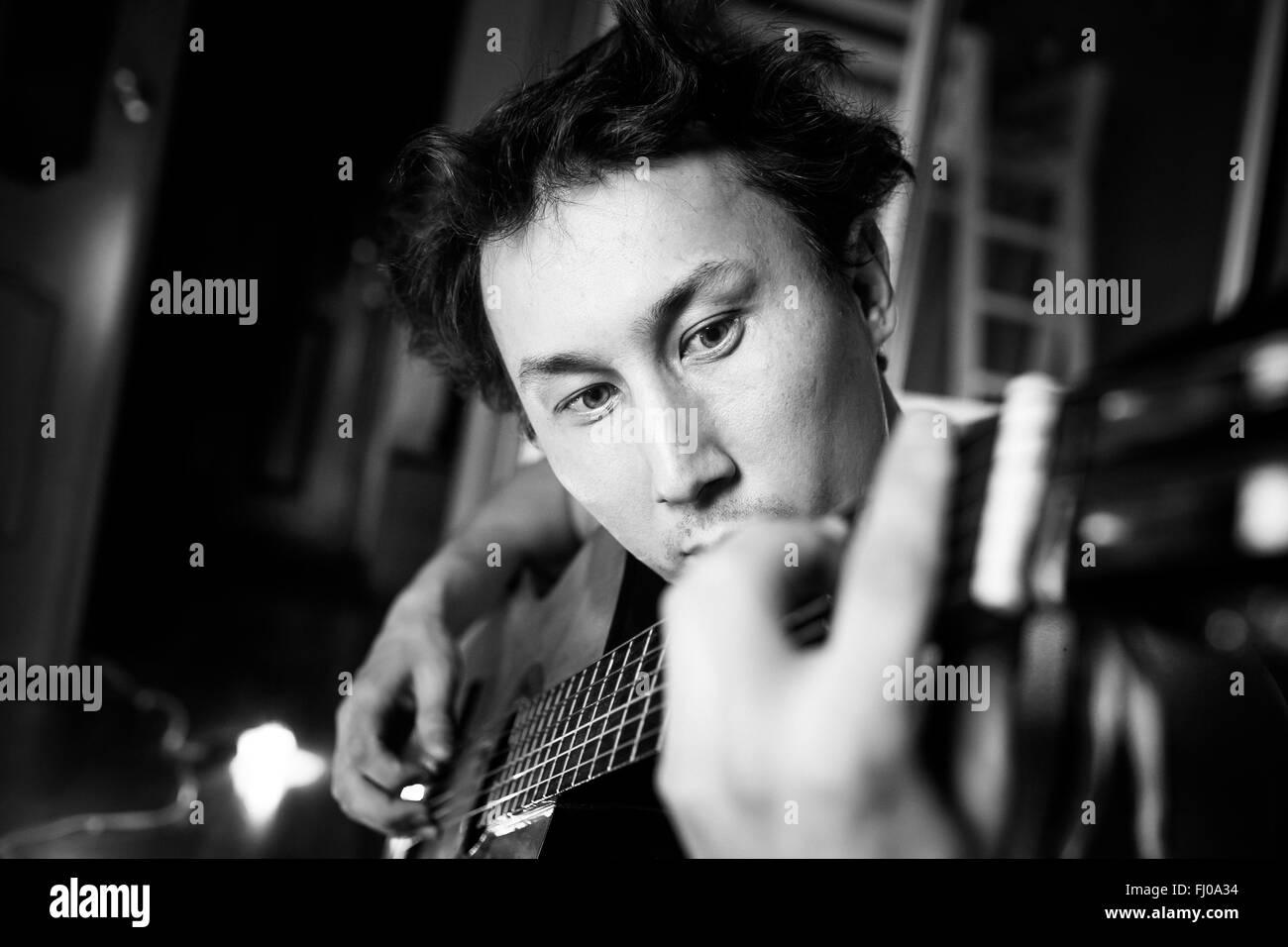 Verrückte leidenschaftliche Gitarrist spielt Gitarre, schwarz / weiß close-up Portrait. Musiker mit zerzausten Stockbild