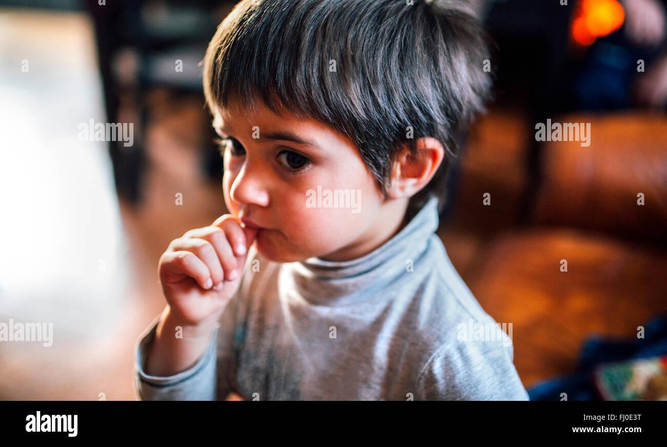Porträt eines kleinen Jungen mit Finger in den Mund Stockbild