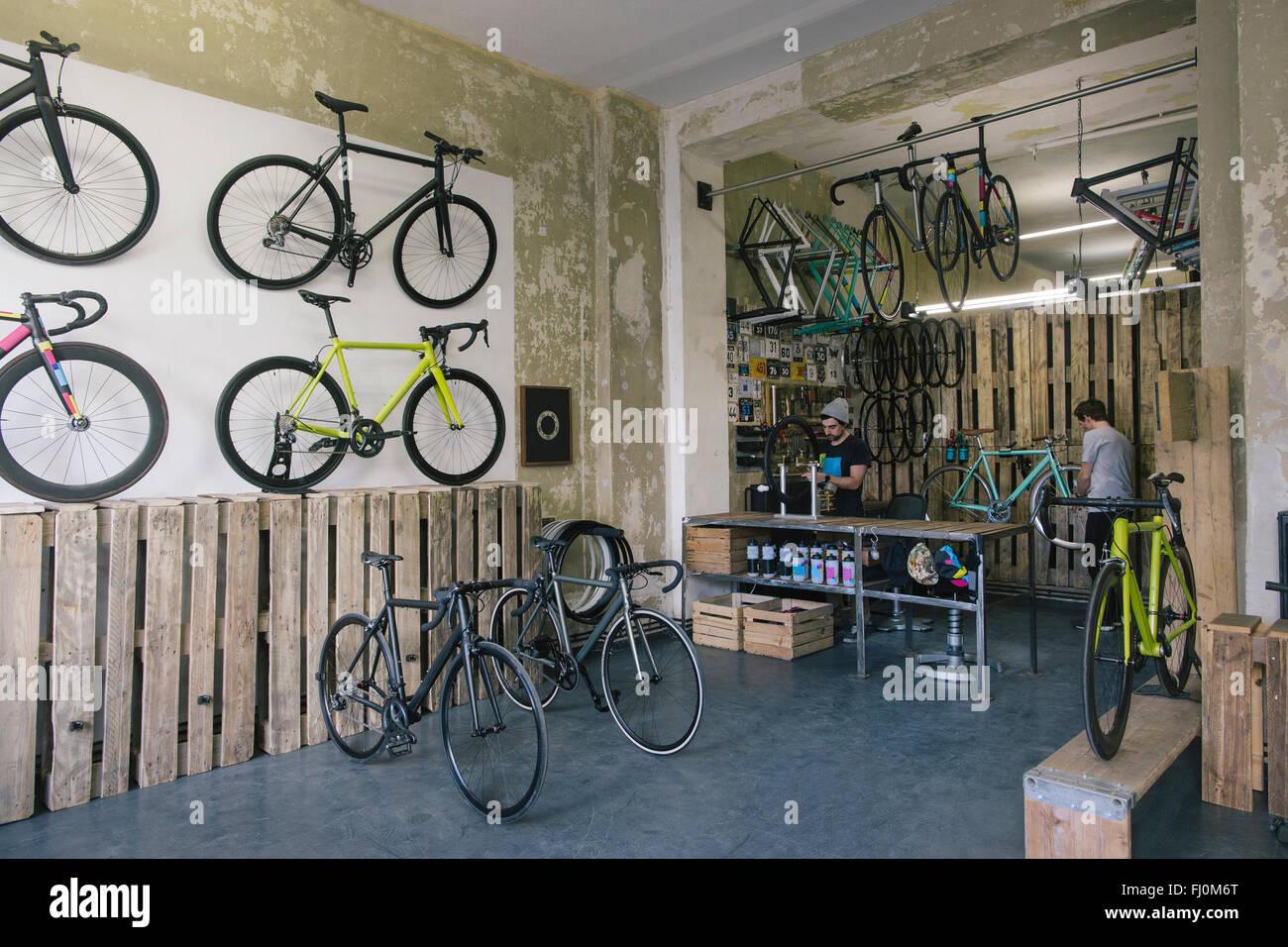 Mechaniker arbeiten in eine maßgeschneiderte Fahrradladen Stockbild