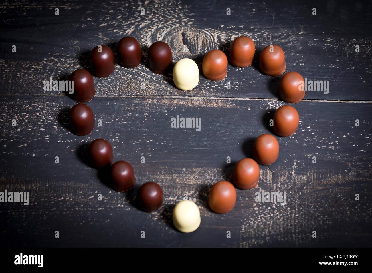 Verschiedene Schokoladen Marshmallows bilden ein Herz auf dunklem Holz Stockbild