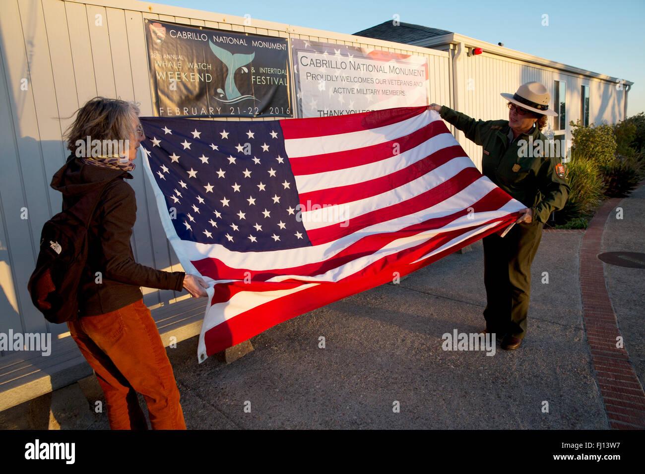 Parkranger und Besucher Faltung der Flagge, Cabrillo National Monument, San Diego, Kalifornien USA Stockbild
