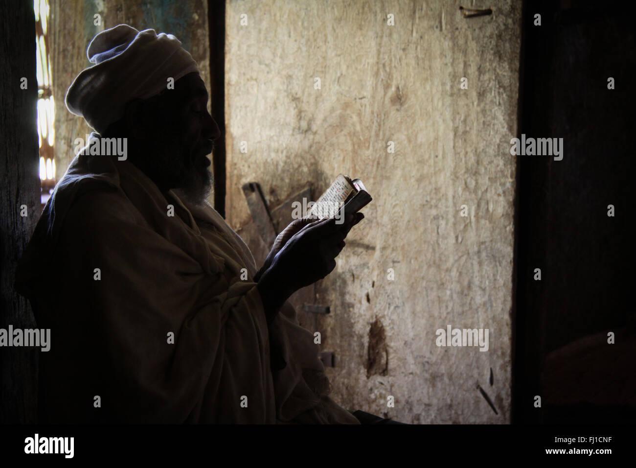 Orthodoxe Priester betet Hintergrundbeleuchtung in Oura Kidane Mehret, Tanasee, Äthiopien, Afrika Stockbild