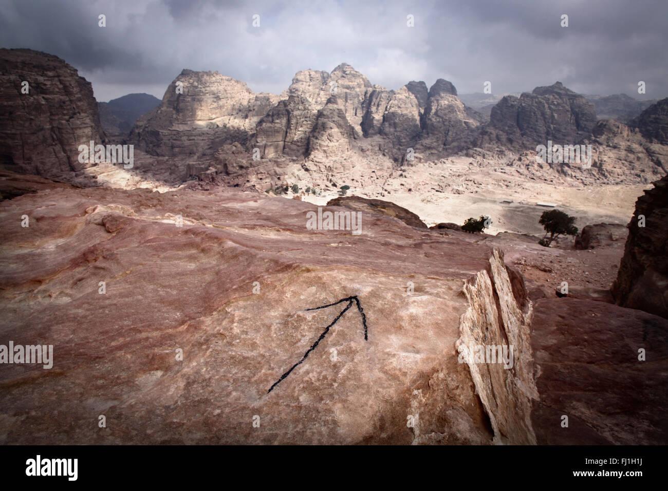 Pfeil gemalt auf Rock zeigt einen Weg auf Jebel al-Madhbah, ein Berg auf der Website von Petra, Jordanien Stockbild