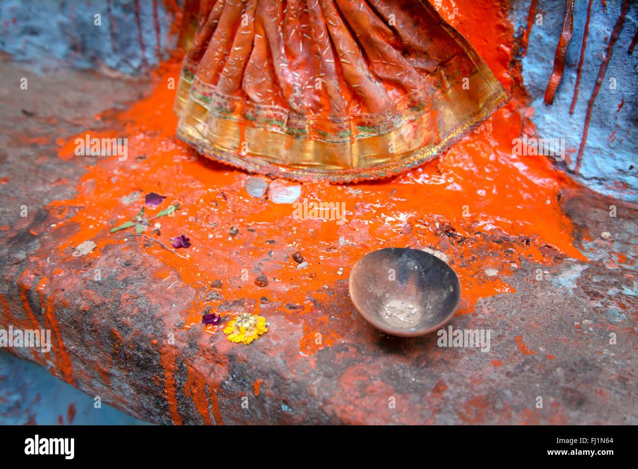 Nahaufnahme auf Rotes Pulver mit Wasser für miwed Puja auf Statue in Varanasi, Indien Stockbild