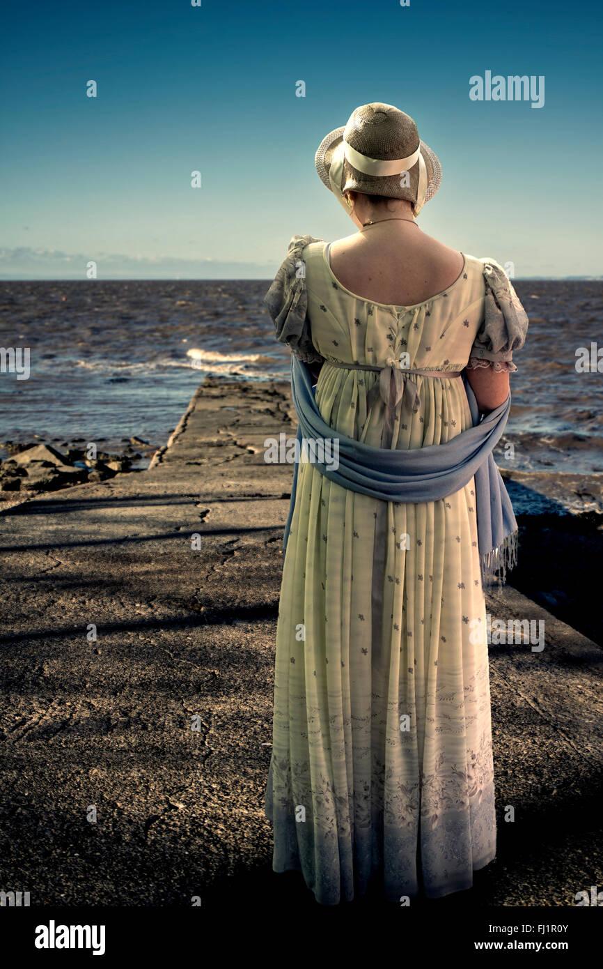 Regency gekleidete Frau, Blick auf das Meer Stockbild