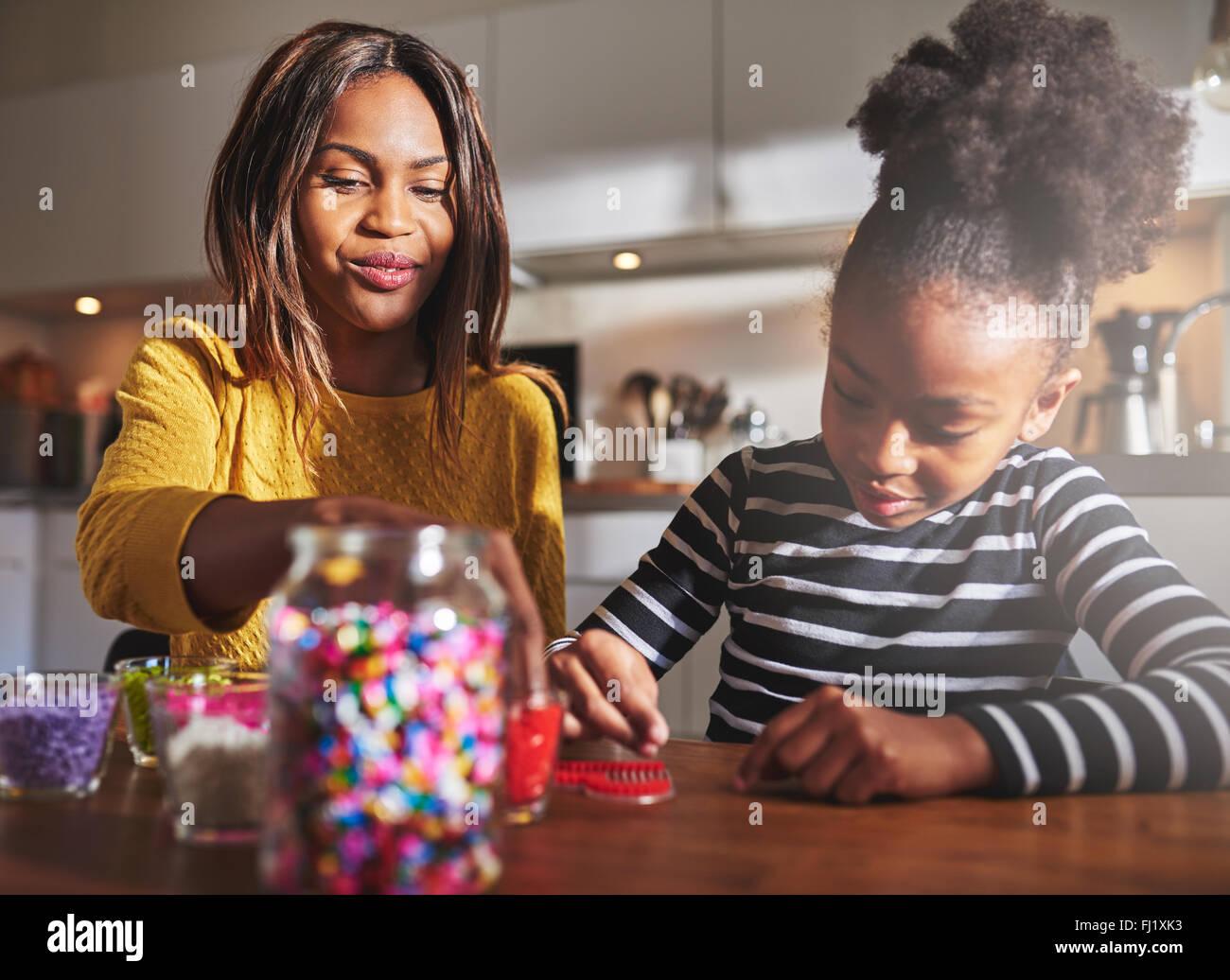 Süße junge Mädchen in gestreiften Hemd macht eine rote Perle Handwerk mit Frau in der Küche Stockbild