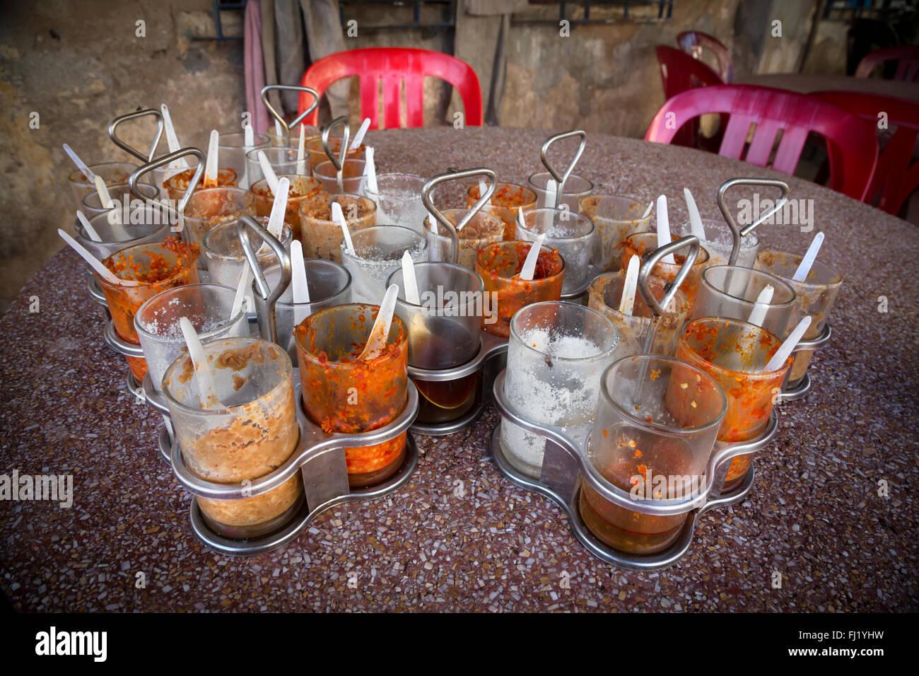 Gewürze und Chili peppers in Gläsern auf einem Tisch in einem Restaurant von Kampot, Kambodscha Stockbild