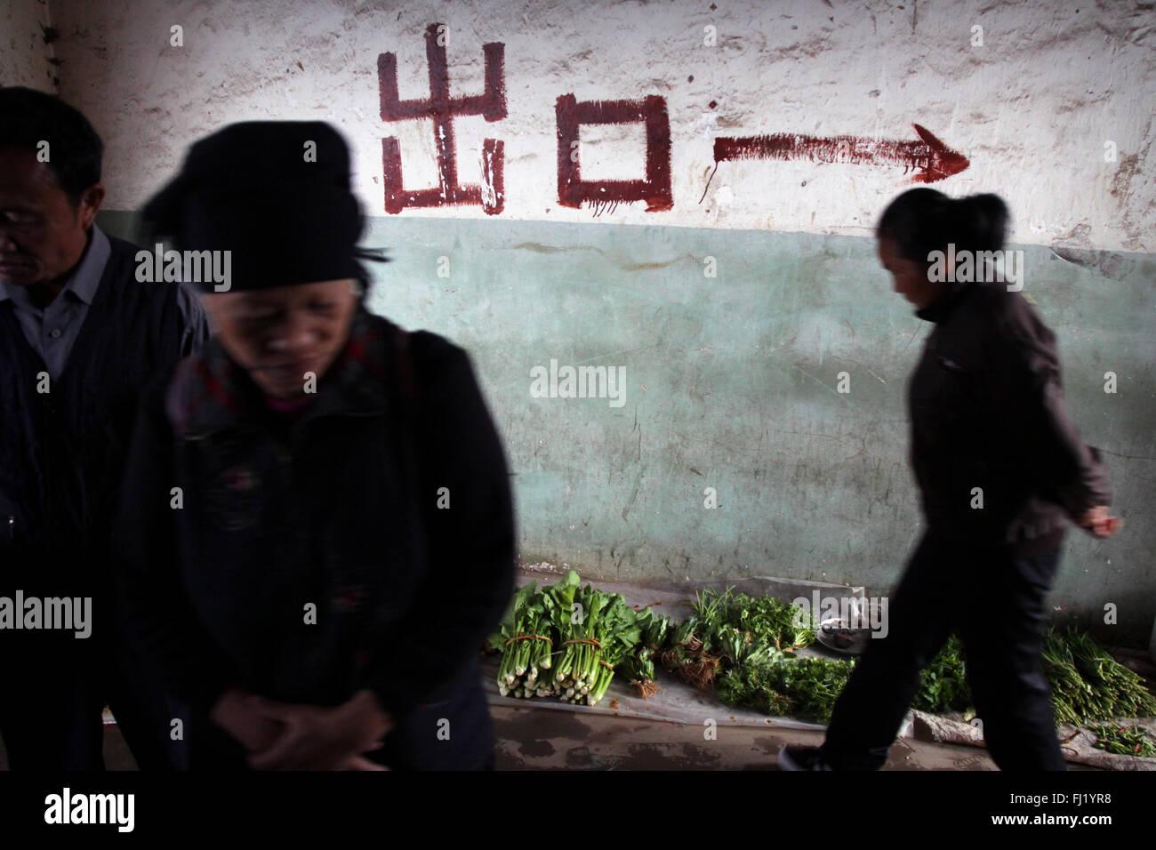 Frauen in Yuanyang Markt mit Pfeil auf einer Wand in Richtung, Yuanyang, China zeigen, lackiert Stockbild