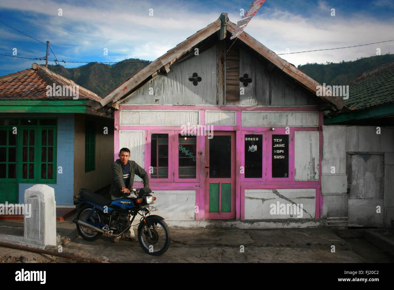Mann vor der traditionellen Holz- Haus im Dorf Cemoro Lawang, Java, Indonesien Stockbild