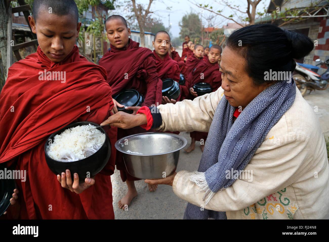 Buddhistische Mönche erhalten Reis aus Bevölkerung, tägliches Ritual, Nyaung-U, Myanmar Stockbild