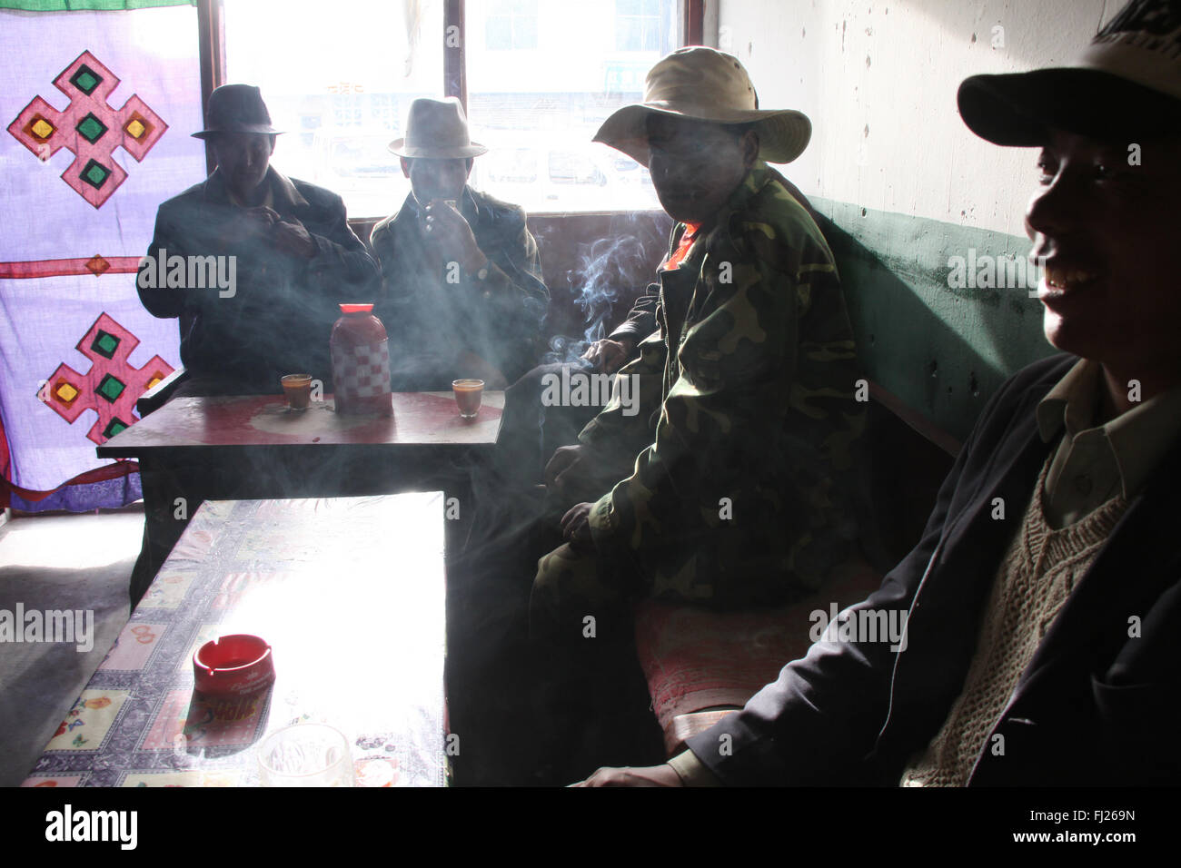 Männer, die Rauchen und Hintergrundbeleuchtung im Café in Tibet Stockbild
