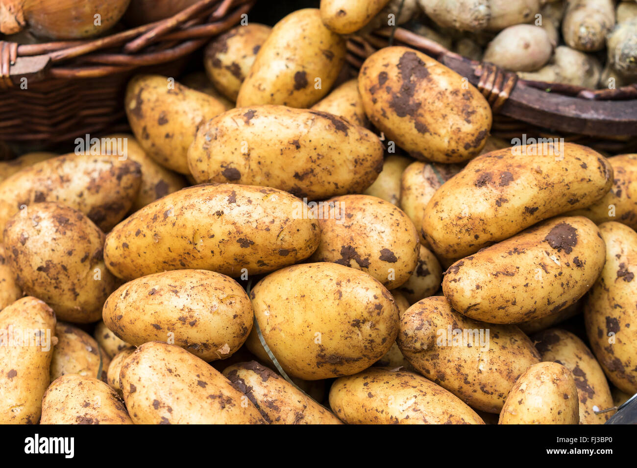 Nahaufnahme eines Korbs von neuen Kartoffeln bedeckt im Boden für den Verkauf auf einem Marktstand Stockfoto