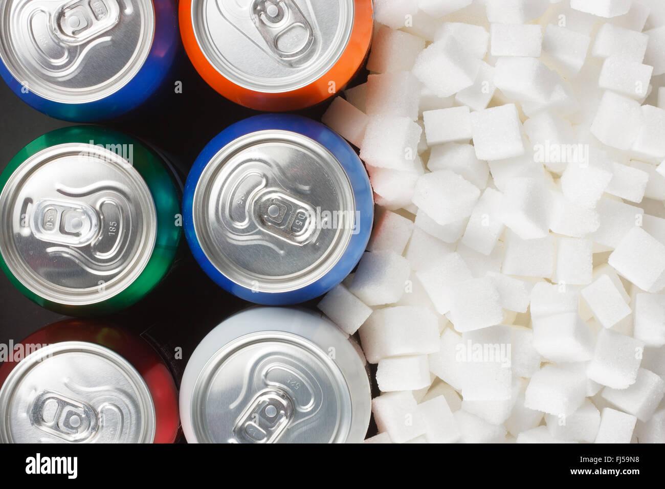 Ungesunde Lebensmittel Konzept - Zucker in Limonaden. Zuckerwürfel als Hintergrund und aus der Dose trinken Stockbild