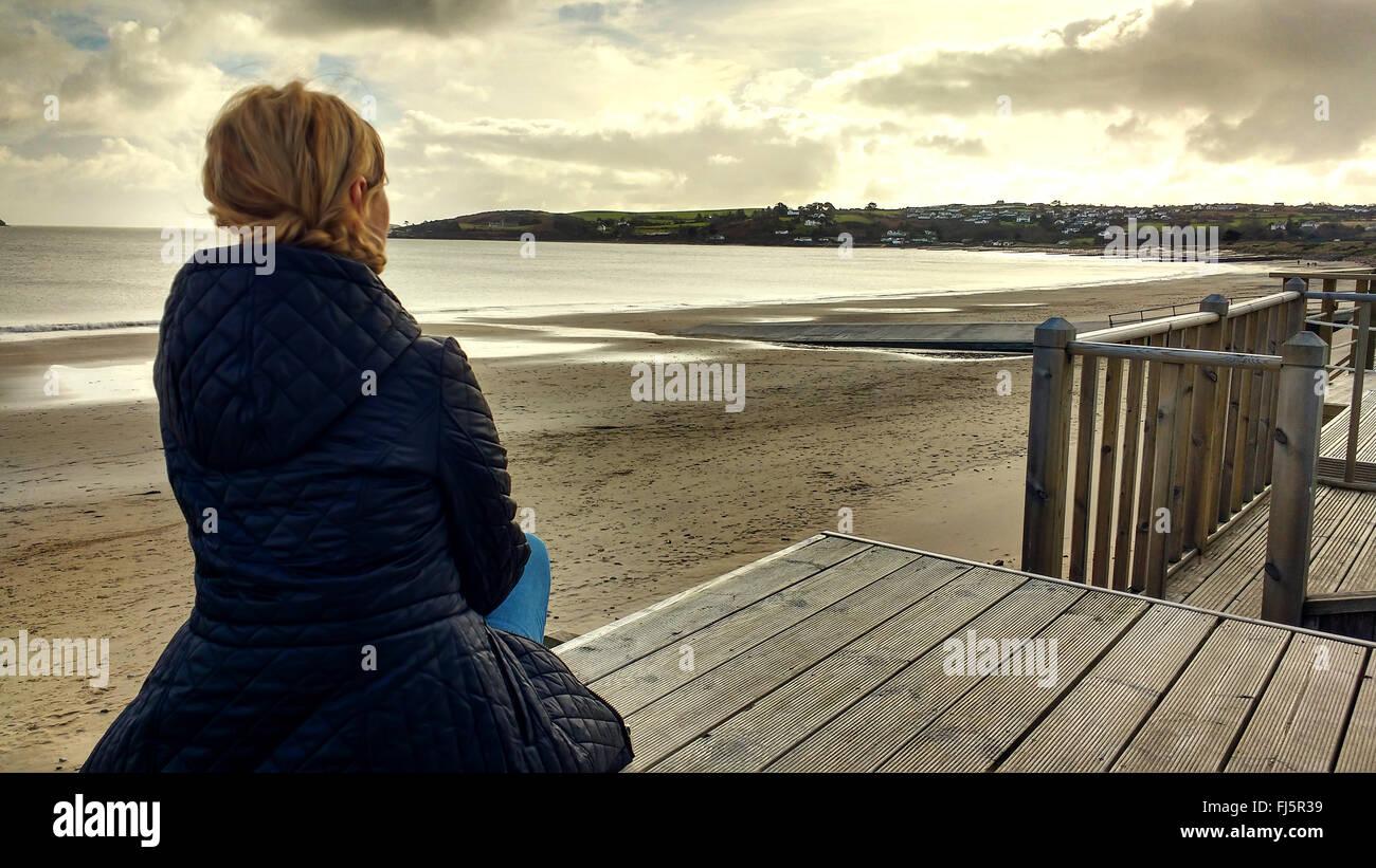 elegante Mädchen sitzen auf Holz am Strand Stockbild