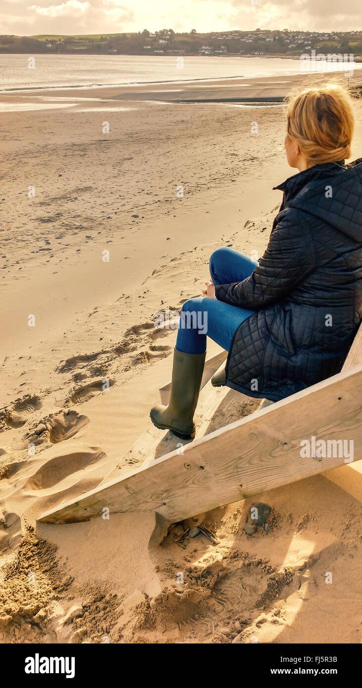 junge blonde Frau sitzt auf der Treppe der Kabine am Strand Stockbild