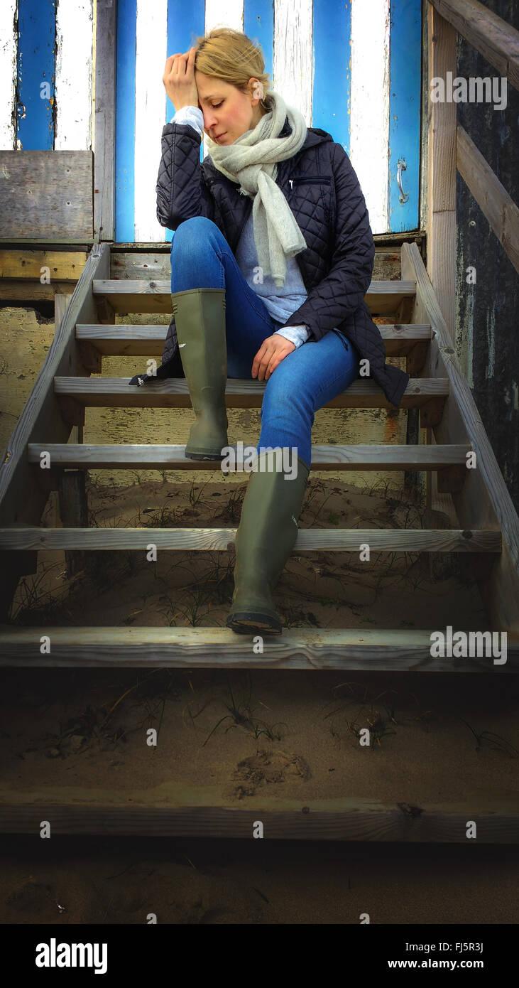 traurige junge Frau sitzt am Strand Kabine Treppen Stockbild