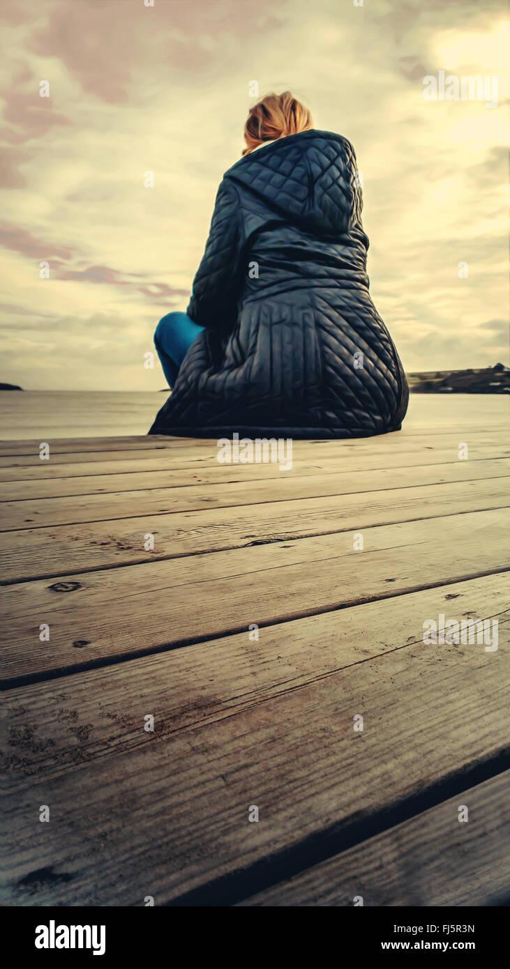 junge blonde Frau, die Standortwahl auf Holzboden am Strand Stockbild