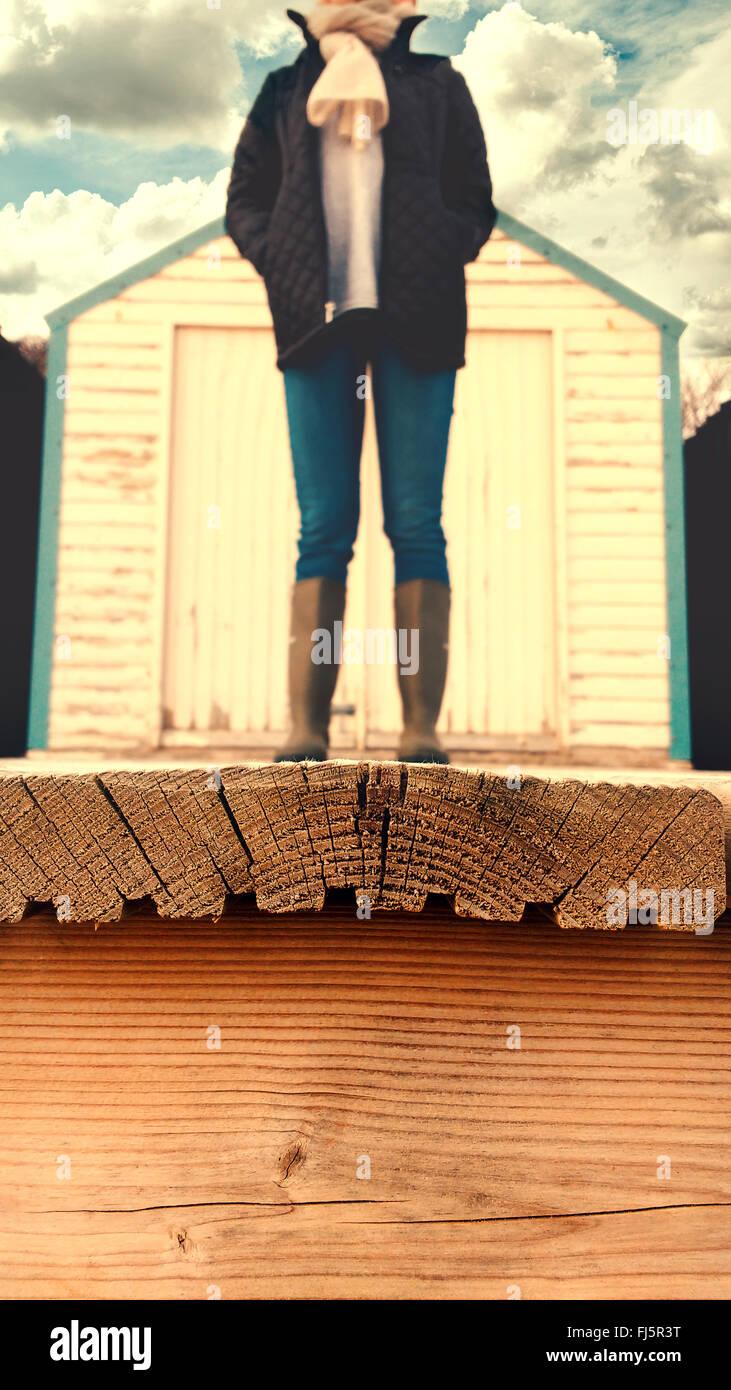 kopflose Frau stand auf dem Holzboden der Strandkabine Stockbild