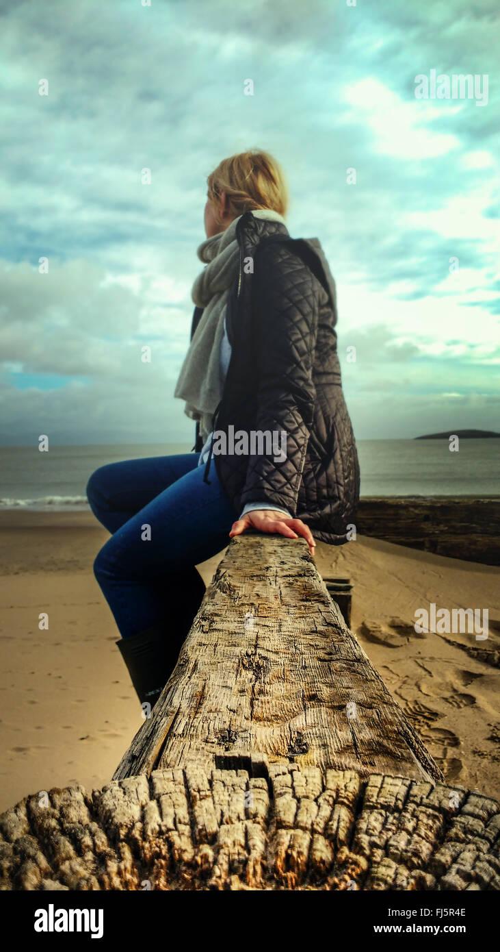 junge Frau sitzt auf Holz am Strand Stockfoto