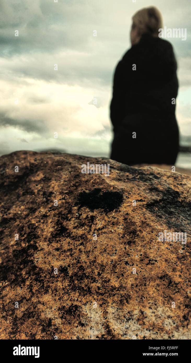 Frau am Strand von den Felsen stehend Stockbild