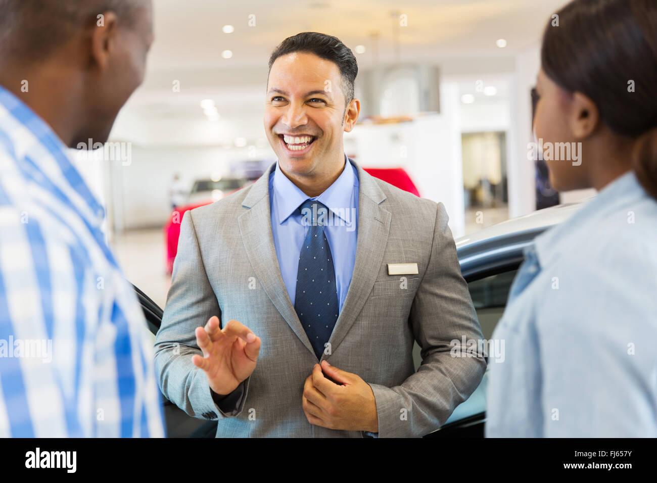 gut aussehend Fahrzeughändler im Gespräch mit Kunden im showroom Stockbild
