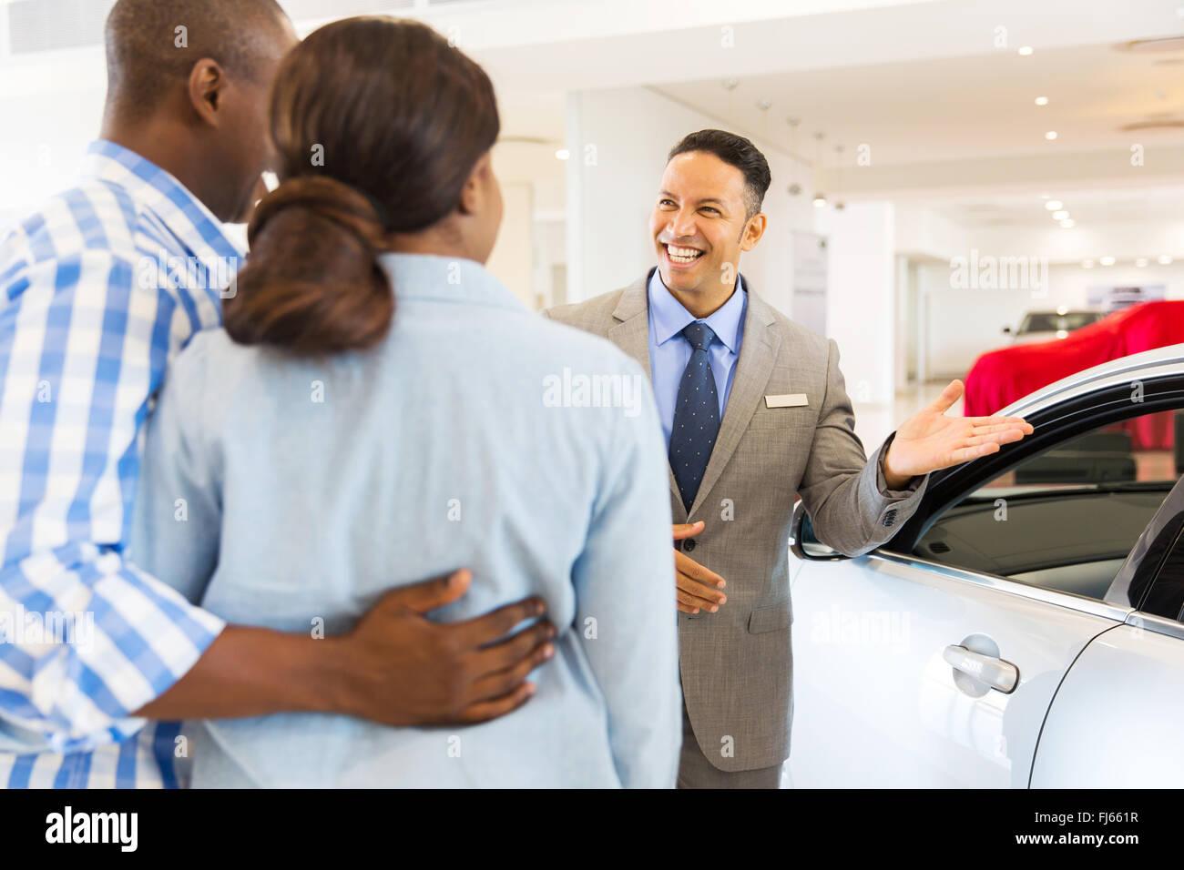 freundliche Händler zeigen neue Auto an Kunden Stockbild