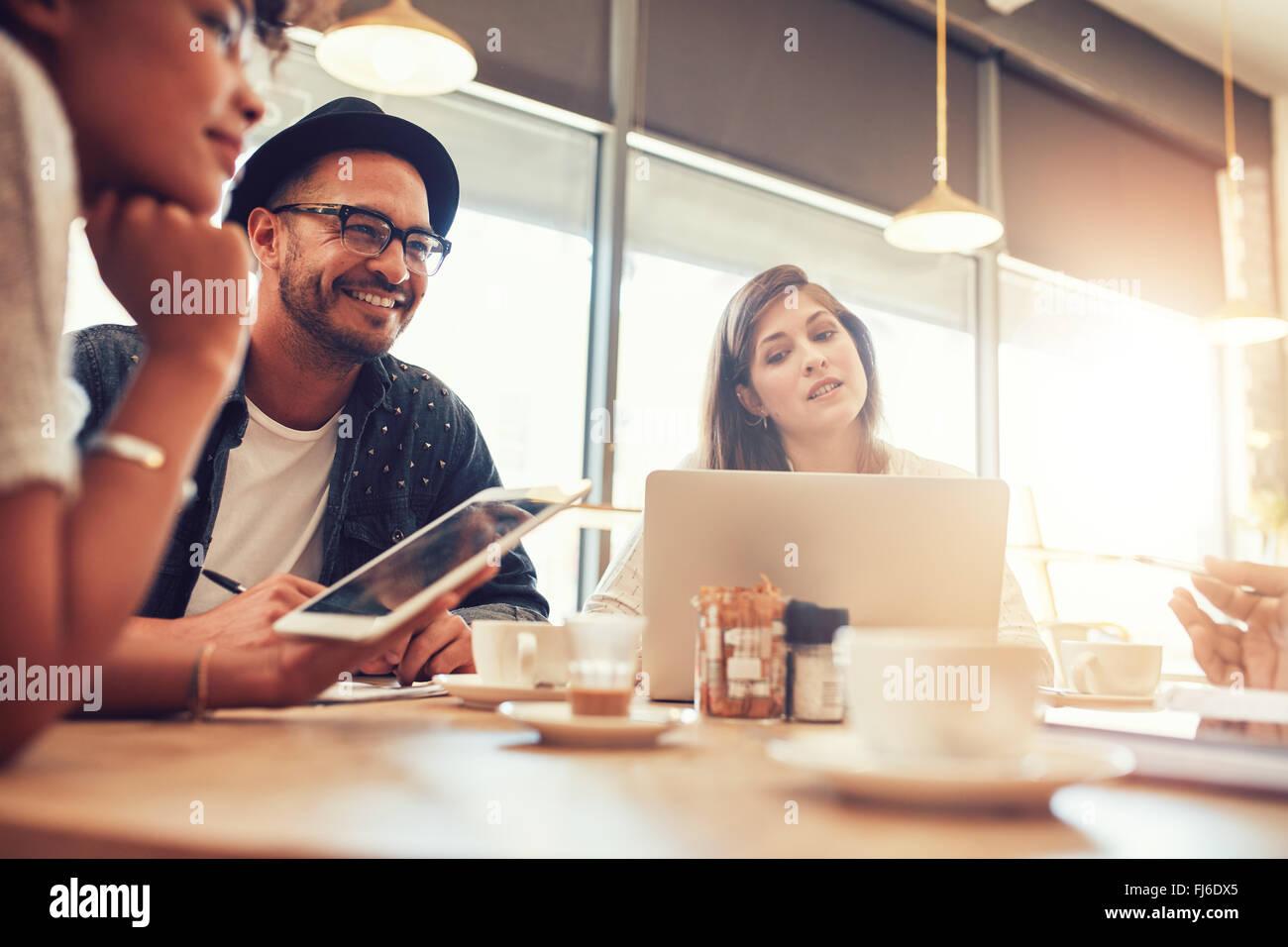 Porträt von glücklicher junger Mann sitzen und reden mit Freunden in einem Café. Junge Menschen in Stockbild