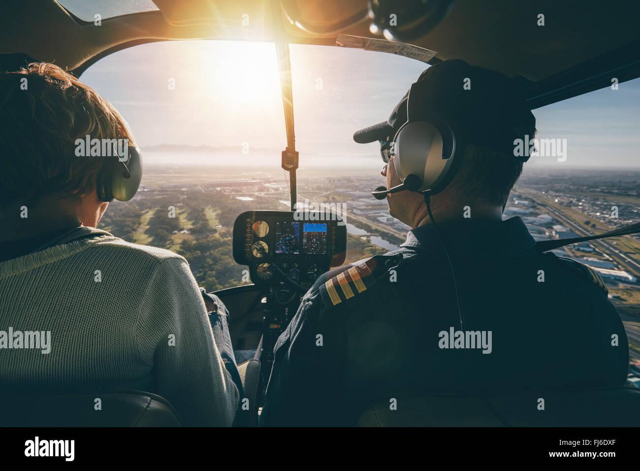 Innenansicht eines Hubschraubers im Flug, mit Mann und Frau-Piloten fliegen eines Hubschraubers an einem sonnigen Stockbild
