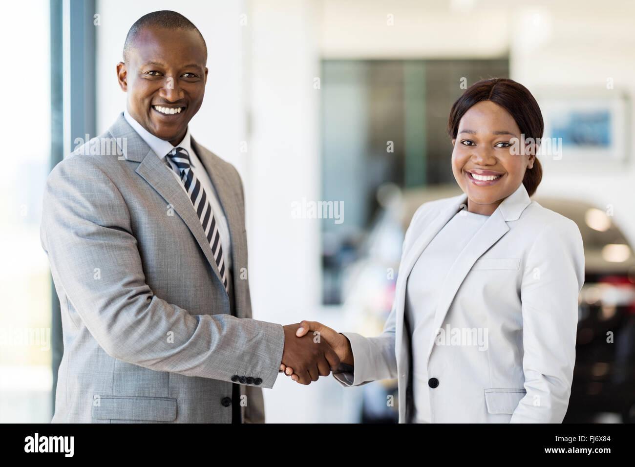schöne Afrikanerin Handshaking mit Kfz-Händler Stockbild