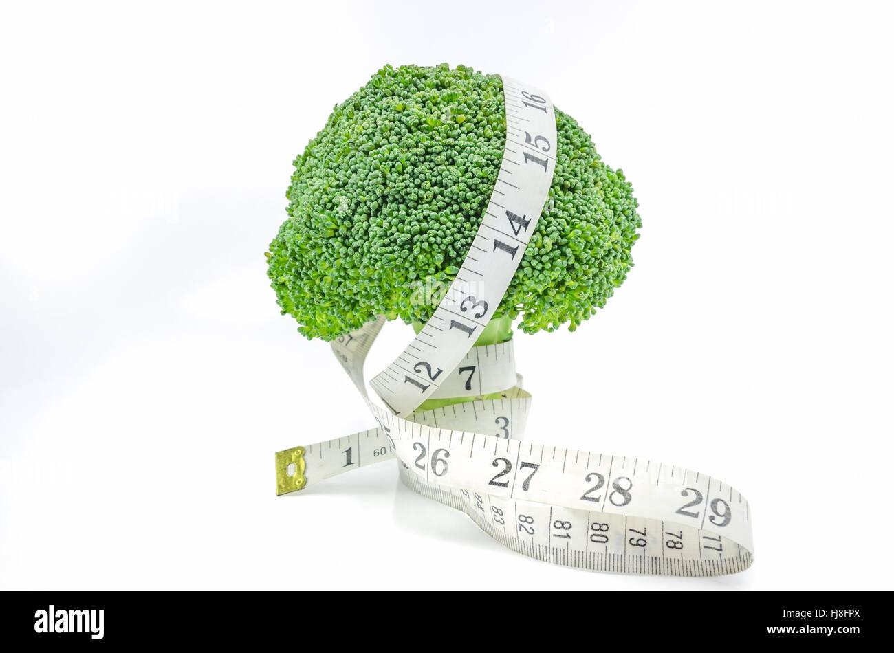 Lebe gesund - frischen rohen Brokkoli mit Maßband auf weißem Hintergrund. Stockbild