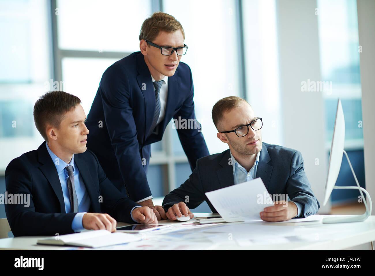 Gruppe von ernsthaften Geschäftsleuten Blick auf Computer-Monitor Tagung Stockfoto